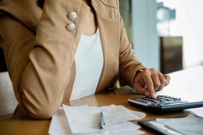 A woman computing her mortgage servicing ratio (MSR) and total debt servicing ratio (TDSR)